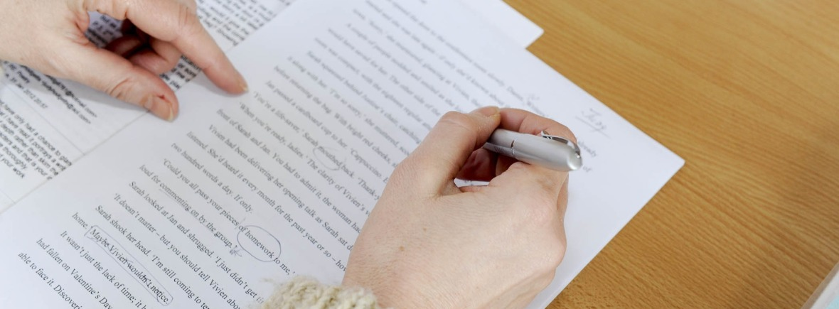A stock photo of a hand holding a pen and making proofreading marks on a story